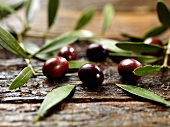 Black olives with leaves on a wooden surface