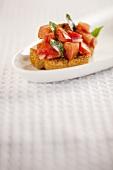 One Bruschetta on a White Plate