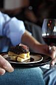 Mann hält Teller mit Straussensteak und Pommes frites und ein Rotweinglas
