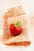 A strawberry on a piece of jute