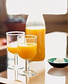 Orange juice in glasses and a bottle