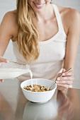 A woman pouring milk onto cornflakes
