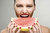 A young woman biting a watermelon