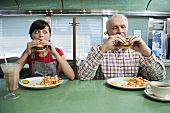 A girl and an old man eating burgers in a diner