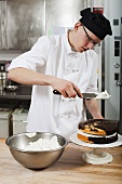 A confectioner icing a cake in a commercial kitchen