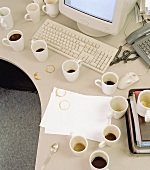White coffee cups in front of a computer