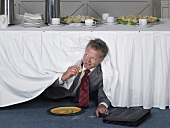 A businessman in a suit eating under a table