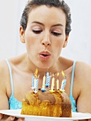 A woman blowing out birthday candles