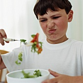 A boy looking disgustedly at a salad