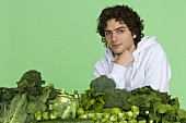 A young man with pile of green vegetables
