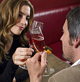 A man and a woman toasting with pink champagne