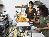 Two women preparing food in the kitchen of a delicatessen
