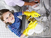A girl helping with the washing up