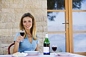 A woman sitting at a table holding a glass of red wine