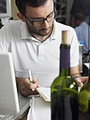 A man using a laptop computer with a bottle of wine in the foreground