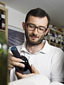 A bearded man with glasses looking at a bottle of wine