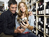 A couple looking at a bottle of wine in a wine shop