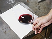 Checking the colour of red wine against white paper