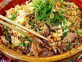 Nasi goreng with meat & spring onions in terracotta bowl