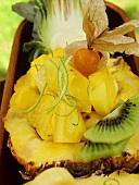 Exotischer Fruchtsalat mit Ananas und Physalis in Holzschale