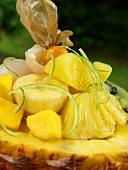 Exotischer Fruchtsalat mit Limettenzesten in Ananashälfte