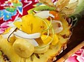 Exotischer Fruchtsalat mit Kokosspänen in Ananashälfte