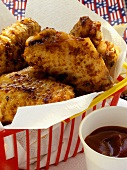 Barbecued chicken wings in plastic basket; barbecue sauce