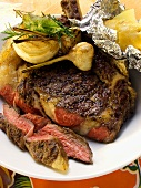 Barbecued ribeye steak with garlic and baked potato