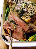Leg of lamb with herbs in roasting dish