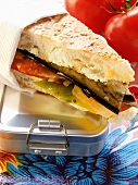 Sandwich with vegetables & cream cheese on lunch box; tomatoes