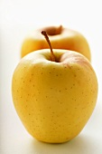 Two Golden Delicious apples, one behind the other