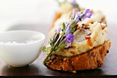 Toasted bread with bean paste, bacon and flowers; salt
