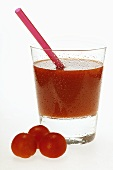 Tomato juice in glass with straw; fresh cherry tomatoes