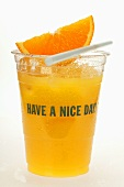Orange juice in plastic tumbler with wedge of orange
