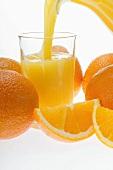 Pouring orange juice; oranges and orange wedges