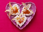 Meringue hearts with physalis & icing sugar on mauve plate