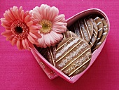 Chocolate cookies in heart-shaped box with flowers