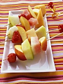Colourful fruit kebabs on platter