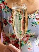 Woman in flowery dress holding champagne glass