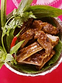 Crispy spare-ribs with fresh herbs in aluminium dish