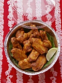 Chicken wings with wedge of lime in aluminium dish