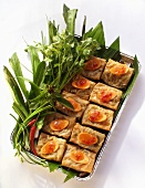 Spring rolls with carrots and herbs in aluminium dish