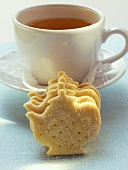 Teapot-shaped biscuit in front of teacup
