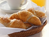 Croissants in bread basket, grapefruit juice & coffee cup