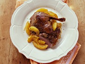 Duck with orange on white plate