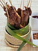 Saté kebabs in basket with leaf; dips