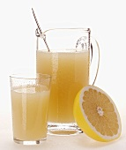 Grapefruit juice in glass and jug beside half grapefruit