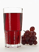 Glass of red grape juice with drops of water & red grapes