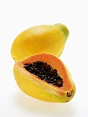 Two papayas, one with a piece cut off