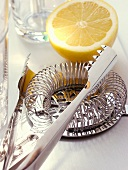 Various bar utensils and lemon